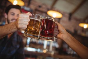 two-young-men-toasting-their-beer-mugs-5WC4RPK-min (1) 0